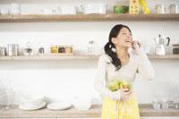 キッチンで携帯電話をしている女性