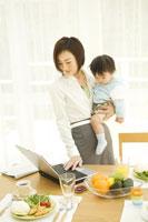 赤ちゃんを抱っこしてパソコンを見る女性