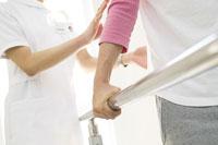歩くリハビリをする男性と看護師の手元