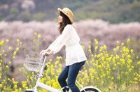 自転車に乗る麦わら帽子をかぶった女性