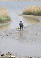 泥地を歩く男性の後姿