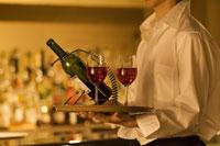 ワインとワイングラスを運ぶウエイター