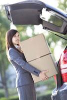自動車に荷物を積み込むビジネスウーマン