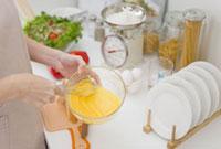 キッチンで卵をかき混ぜる女性の手