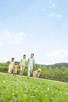 公園を散歩する家族と犬