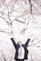 桜の木下でアタッシュケースを投げている新入社員