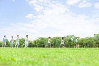 芝生でジョギングをしている3世代家族
