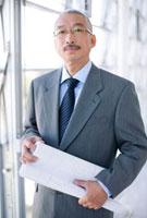 設計図を抱える中高年ビジネスマン 07800011968| 写真素材・ストックフォト・画像・イラスト素材|アマナイメージズ