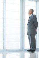 窓の外を見ている中高年ビジネスマン