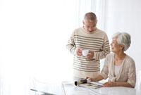 雑誌を見て会話する中高年夫婦