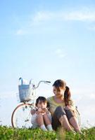 芝生に座ってハーモニカを吹く女の子と母親