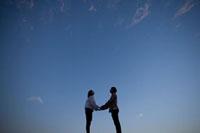 手を取り合うカップルのシルエット