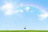 虹のかかった青空の下を走る子供