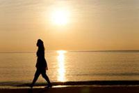 海辺を歩く若者女性のシルエット