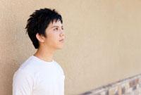壁の前で考え事をする若者男性