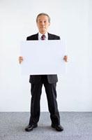 メッセージボードを持つ中高年ビジネスマン