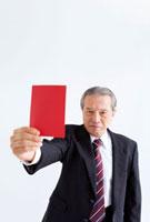 レッドカードを持った中高年ビジネスマン
