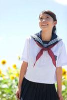 笑顔の女子学生とヒマワリ畑