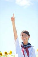 人差し指を立てる笑顔の女子学生とヒマワリ畑