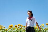 両手を広げる笑顔の女子学生とヒマワリ畑