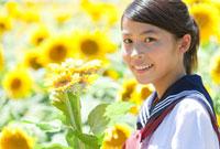 ヒマワリを持っている女子学生とヒマワリ畑