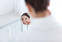 鏡を見ている中高年女性の後姿