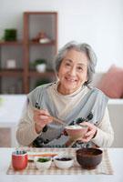 朝食を食べる笑顔の老人女性