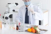 試験管を見る男性研究者