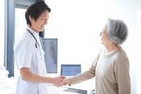 握手する男性医師とシニア女性