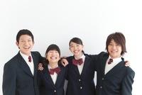 肩を組んでいる笑顔の男女中高生4人