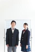 ホワイトボードの前に立っている男女中高生2人