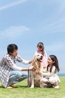 犬を撫でている父と娘