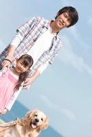 海岸に立っている父と娘と犬