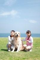 芝生でしゃがんでいる女の子2人と犬