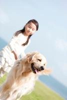 芝生を散歩する女の子と犬