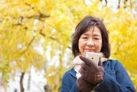 スマートフォンを操作する中高年女性