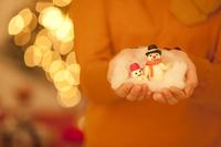 雪だるまの人形を手に乗せている女性