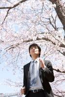 桜の木の下で走っているビジネスマン