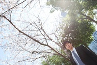 桜の木の下に立っているビジネスマン