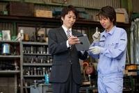 タブレットPCを見せるスーツの男性と作業着姿の男性