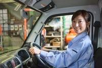 軽トラックに乗っている作業着姿の女性