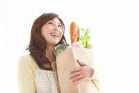 買い物袋を抱えているエプロン姿の女性