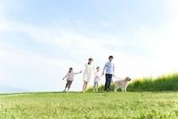 手をつないで歩く4人家族と犬