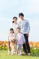 花畑で笑顔の4人家族と犬