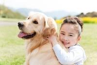 犬に抱きつく笑顔の女の子