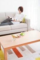ソファーで本を読む女性