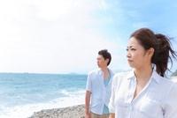 砂浜に立って遠くを眺めているカップル