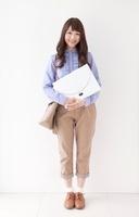 書類を抱えて立つ女性