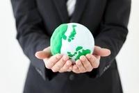 地球儀を手に乗せているビジネスマン
