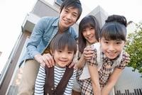 家の前に立つ家族4人
